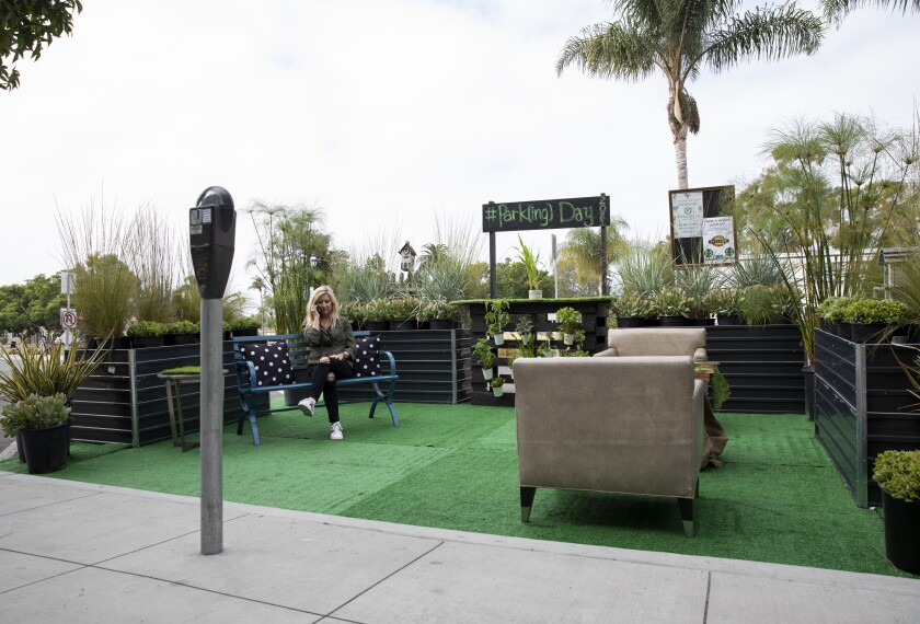 Kelly Lannom, interim executive director for Third Avenue Village Association, makes a call in a newly transformed parklet.