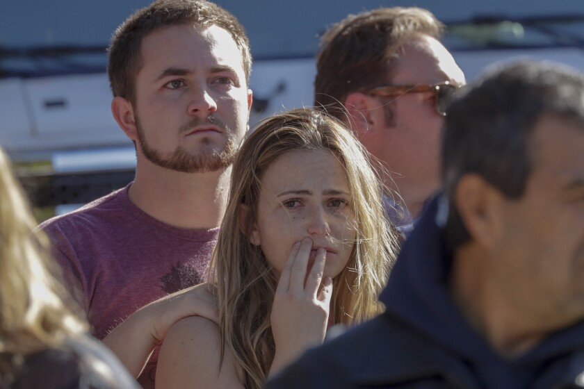 Harrison King, 24, and Alexis Tait, 23, stand on the roadside as a hearse carrying the body of Ventura County sheriff's Sgt. Ron Helus leaves in a procession. King and Tait escaped the shooting at Borderline, but one of their friends was killed.