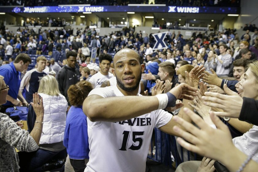 Xavier's Myles Davis (15) greets fans after their NCAA college basketball game against Creighton, Saturday, March 5, 2016, in Cincinnati. Xavier won 98-93. (AP Photo/John Minchillo)