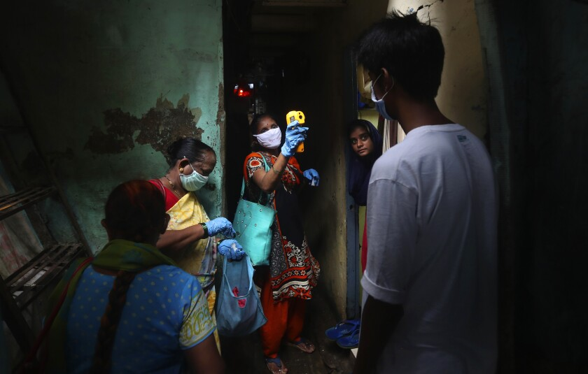 A healthcare worker checks people for COVID-19 symptoms in Dharavi, one of Asia's biggest slums, in Mumbai, India.