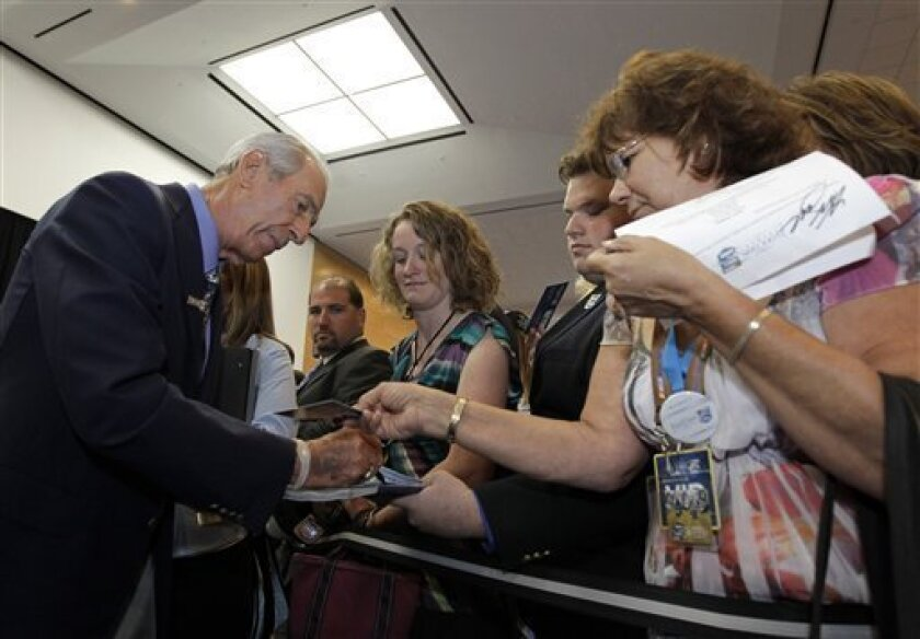 Ned Jarrett, left, signs autographs for fans as he arrives for the NASCAR Hall of Fame induction ceremony in Charlotte, N.C., Monday, May 23, 2011. Jarrett is one of five inductees. (AP Photo/Chuck Burton)
