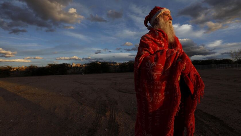 James Zyla, 68, stands in the late afternoon light wrapped in a red blanket across from where he is staying at the Ramada hotel in Kingman, Ariz. For years, the white-bearded man in the Santa Claus outfit has been a familiar sight around this isolated high desert town.