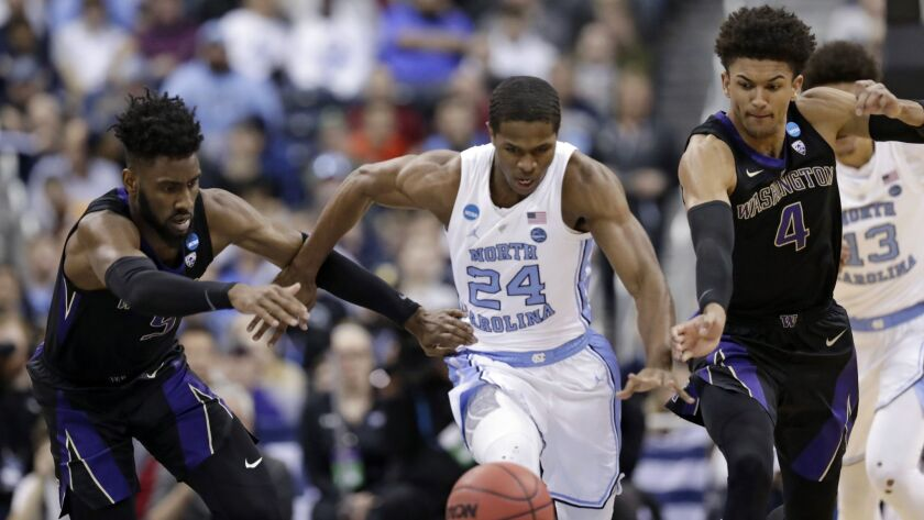 North Carolina's Kenny Williams, center, chases after a loose ball ahead of Washington's Jaylen Nowell, left, and Matisse Thybulle during the Tar Heels' second-round win in the NCAA tournament on Sunday.