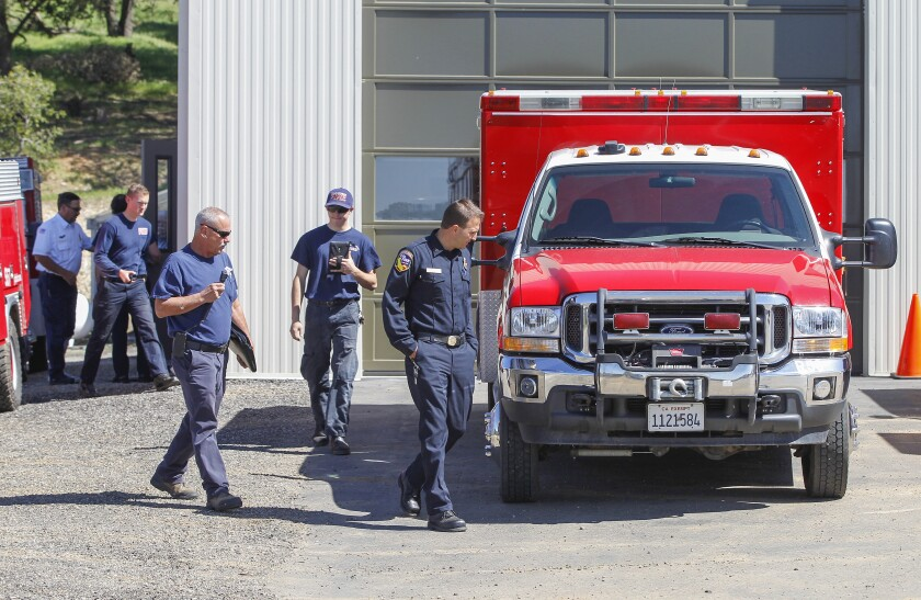 Cal Fire battalion chief Jeremi Roesler (right) and SD County Fire Authority fire services coordinator Kevin O'Leary (left) inspect a truck at the Julian volunteer fire department with volunteers (middle, and background) during the first inspection of the fire department.
