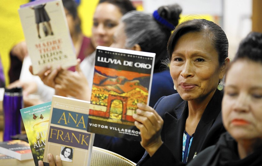 Cleotilde Flores, center, holds her favorite books that she has read with other mothers at the Bravo Medical Magnet High School literature club.