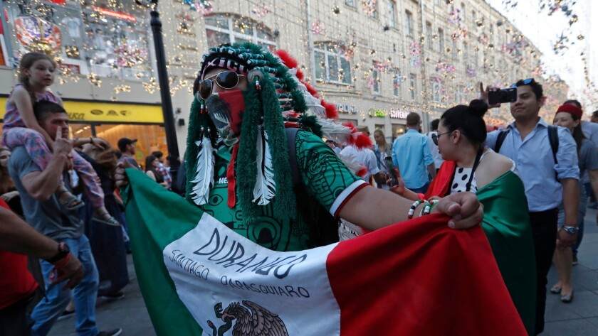 "A fan of Mexico walks on Nikolskaya Street near the Kremlin, dubbed the ""Street of Light,"" one of the favorite meeting points in the Russian capital for soccer fans during the 2018 FIFA World Cup."