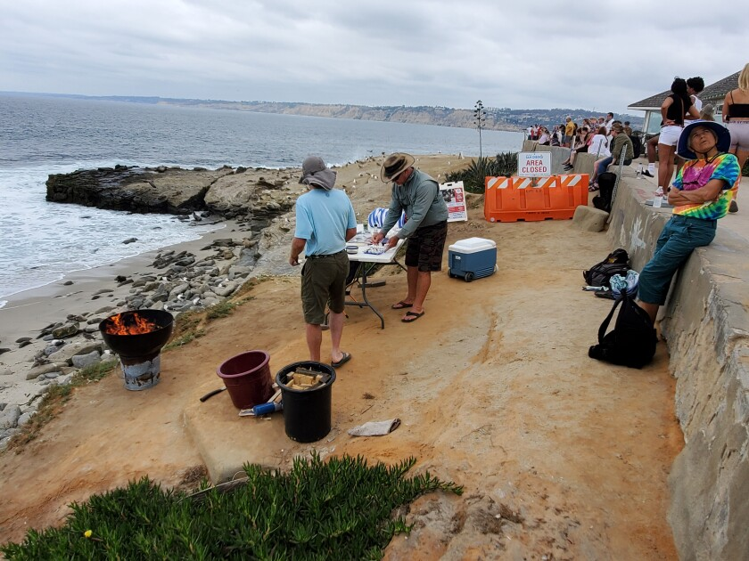 Beach access advocates and bodysurfers gather for a barbecue at the trailhead to Boomer Beach.