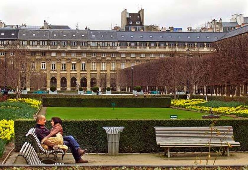 A couple enjoys the park with the Palais-Royal in Paris, in background, where Colette lived at the end of her life and was given a state funeral when she died in 1954.