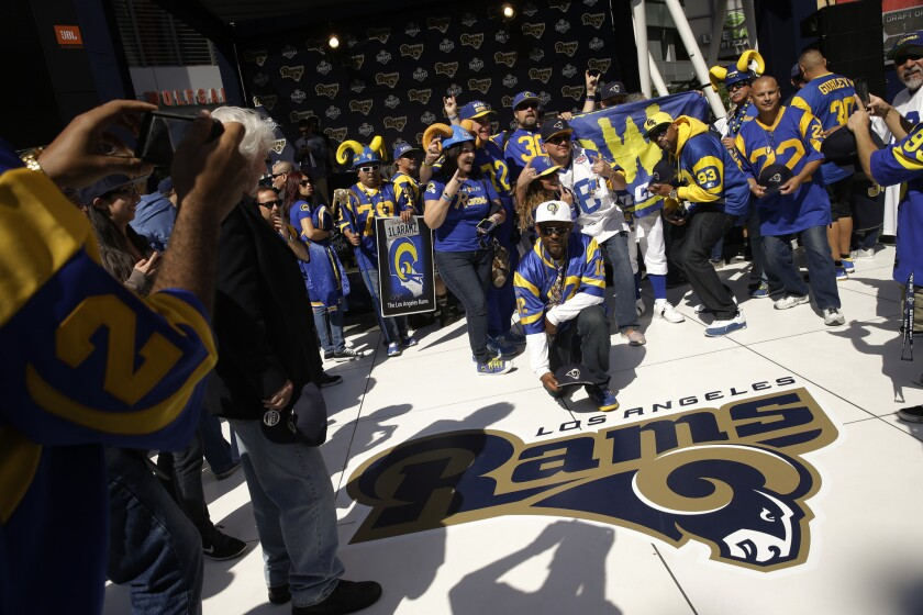 Rams fans pause for photos next to the team's logo at a draft party on April 28, 2016 at L.A. Live.