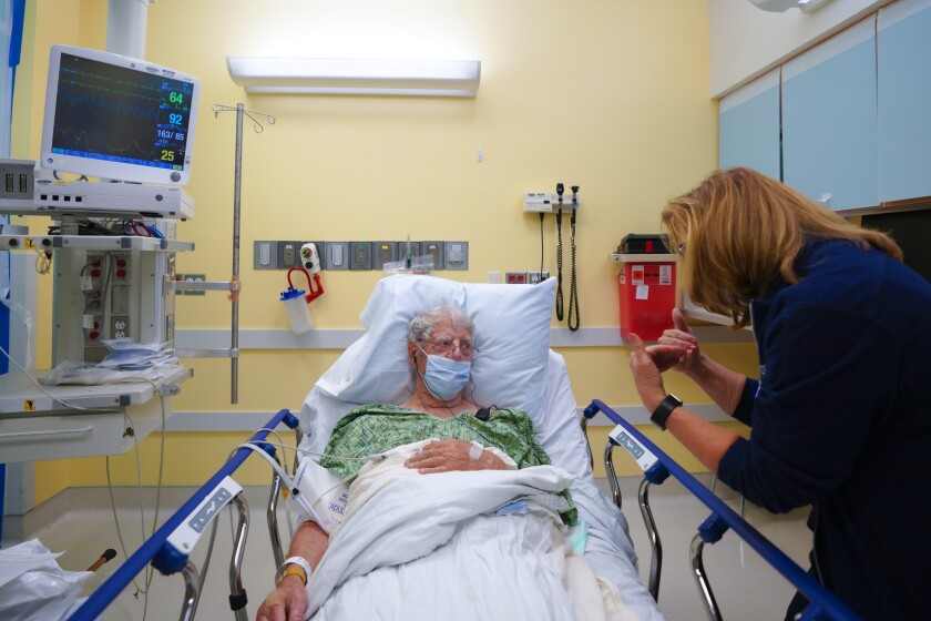 An RN gives an assessment evaluation to her patient in the emergency room.