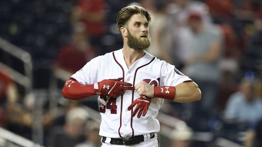 Washington Nationals' Bryce Harper takes off his batting gloves after he was called out on strikes d
