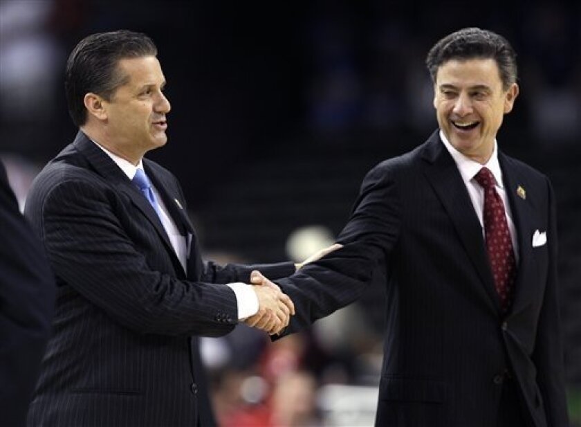 CORRECTS RICK PITINO AT RIGHT, NOT LEFT - Louisville head coach Rick Pitino, right, shakes hands with Kentucky head coach John Calipari before the first half of an NCAA Final Four semifinal college basketball tournament game Saturday, March 31, 2012, in New Orleans. (AP Photo/David J. Phillip)