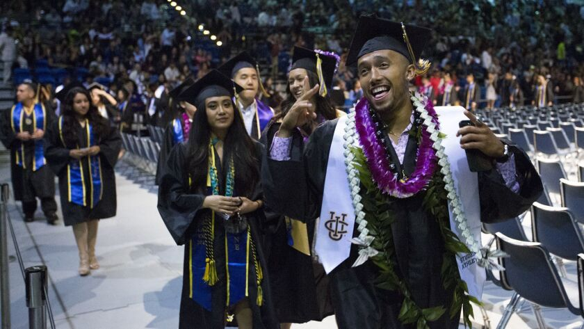 A graduate waves to the crowd during the recessional of the 2017 commenement ceremony for the School