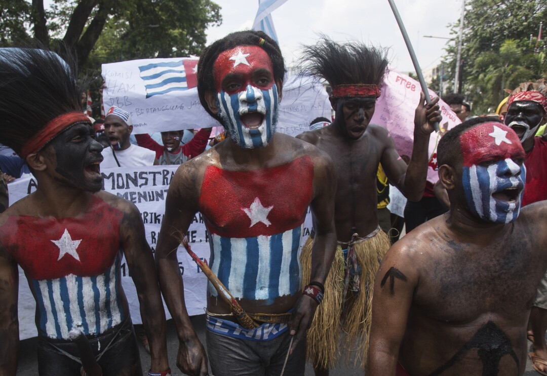 Papuan students with their bodies and faces painted with the colors of the banned separatist Morning Star flag.