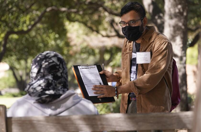 Hector Andres, un organizador del grupo de empoderamiento hispano JOLT, ofrece registros para votar durante un acercamiento a la comunidad en Arlington, Texas, el miércoles 22 de 2021. (AP Foto/LM Otero)