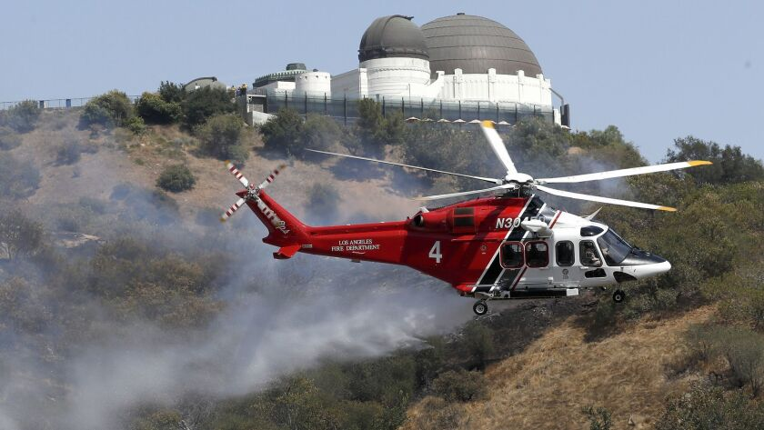LOS ANGELES, CALIF. - JULY 10, 2018. A Los Angeles City Fire Department heliciopter drops water on
