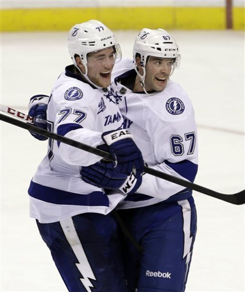 Tampa Bay Lightning's Benoit Pouliot (67) is congratulated by teammate Victor Hedman (77) after Pouliot scored the game winning goalin a 6-5 win in overtime against the Florida Panthers in an NHL hockey game in Sunrise, Fla., Saturday, Feb. 16, 2013. (AP Photo/Alan Diaz)