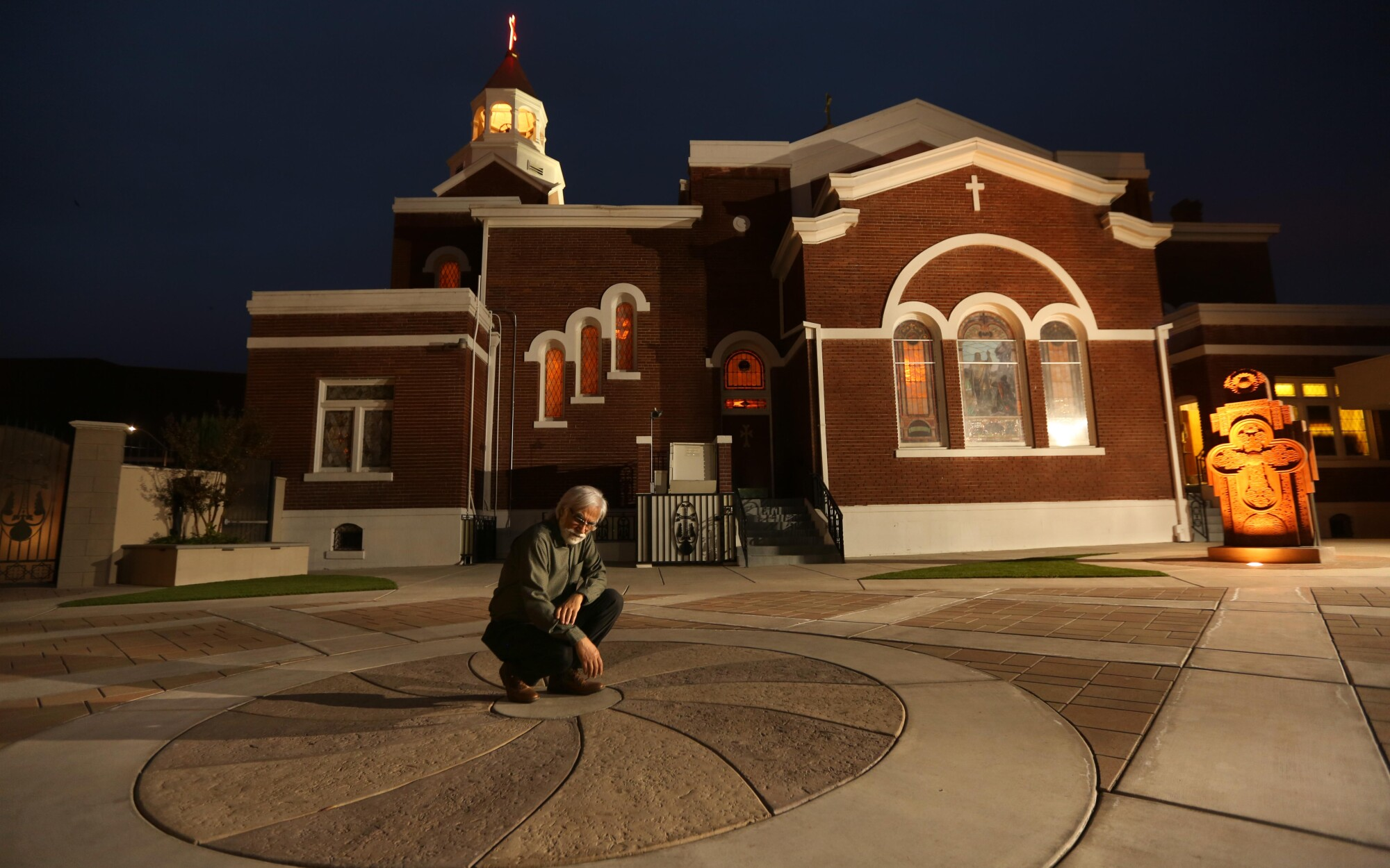 Varoujan Der Simonian kneels in the center of a concrete design outside a church