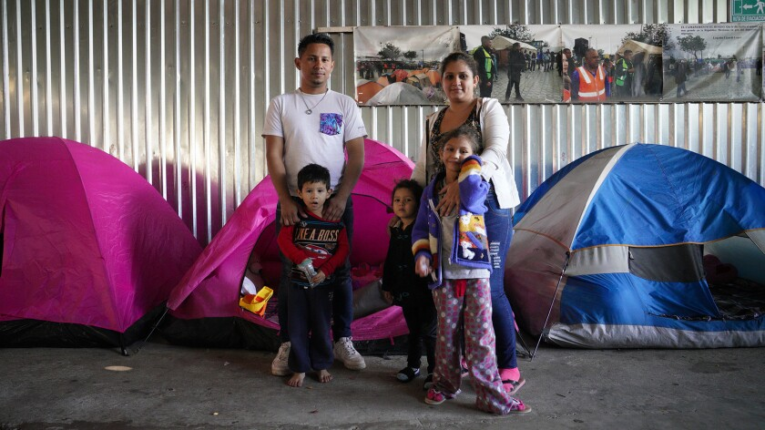 David Enamorado, 32, from Honduras shares a small tent with his family at the Movimiento Juventud shelter in Tijuana. Enamorado is waiting for his asylum request to be processed in the U.S. With Enamorado is his wife, Wendy, 24, and their children.
