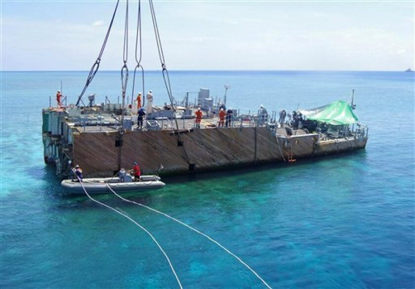 FILE - In this March 29, 2013 photo released by the Philippine Coast Guard, workers prepare for lifting of a part of the dismantled hull of the USS Guardian on the Tubbataha Reef, a World Heritage Site in southwest of the Philippines. Workers in the southwestern Philippines have removed the last ma