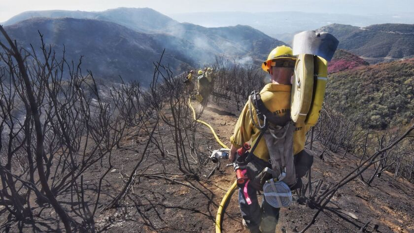 Santa Barbara County firefighters snuffing out hot spots from the Thomas fire drag hose down a steep hillside below East Camino Cielo near Montecito.
