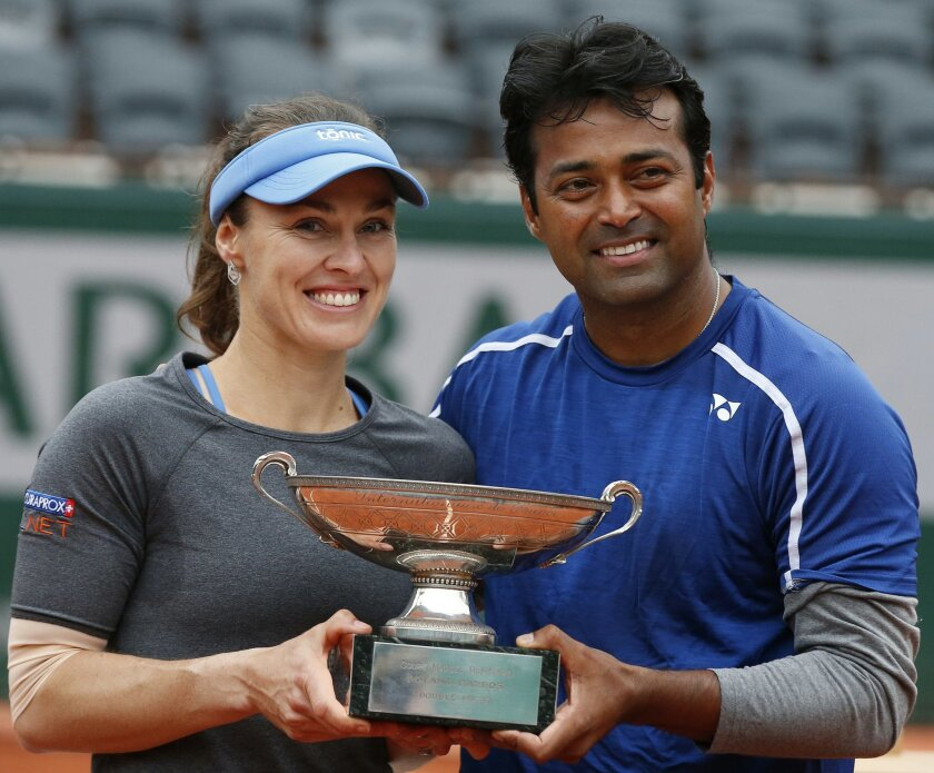 Switzerland's Martina Hingis, left, and India's Leander Paes hold the trophy after winning the mixed doubles final of the French Open tennis tournament against India's Sania Mirza and Croatia's Ivan Dodic at the Roland Garros stadium in Paris, France, Friday, June 3, 2016. (AP Photo/Alastair Grant)