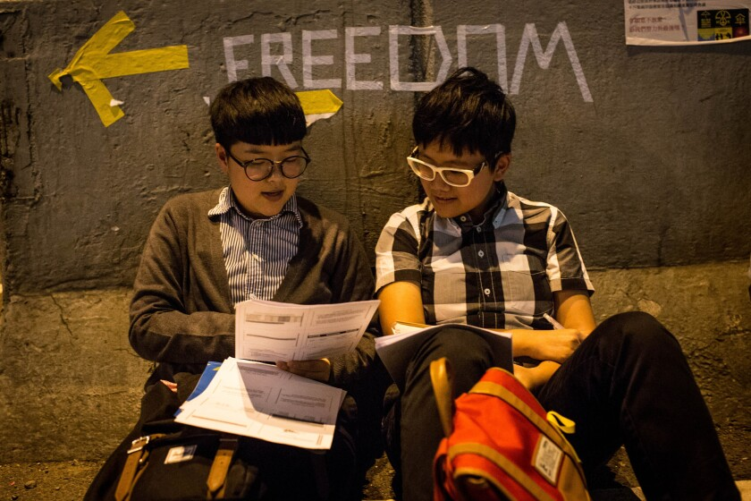 Two university students study on the street outside Hong Kong's government complex.