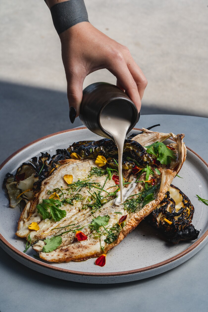 Wood-fired sea bass with charred cabbage and shishito peppers and a coconut lime leaf broth at VAGA Restaurant in Leucadia.