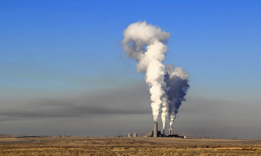 A layer of haze looms west of the Four Corners Generating Station in New Mexico. Southern California Edison recently sold its stake in the power plant, but the facility still burns coal to produce power that goes to Arizona customers instead.