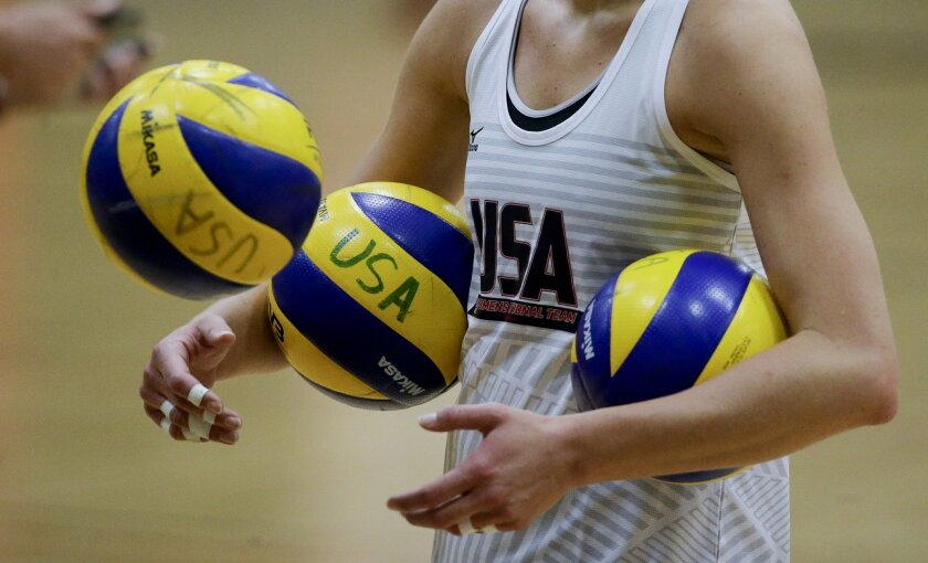 In this Tuesday, May 24, 2016, photo, Jordan Larson gathers up balls during U.S. women's national volleyball team practice in Anaheim, Calif. When the U.S. women's volleyball team got together months ago, the coaches embarked on a risky experiment: Evaluate your teammates. It paid off in a stronger
