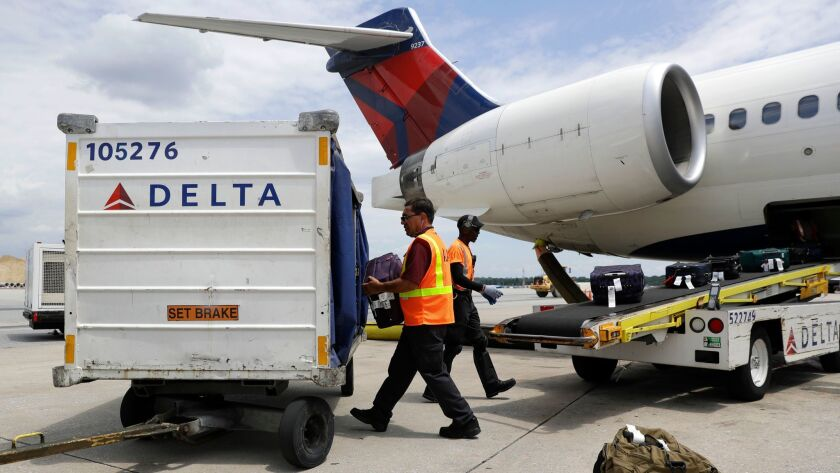 Workers unload baggage from a Delta Air Lines flight at Baltimore-Washington International Thurgood Marshall Airport.
