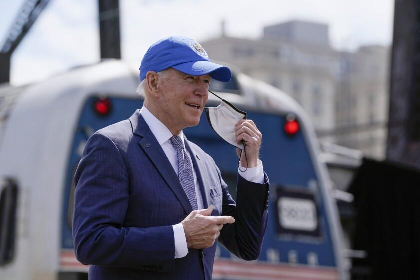 El presidente Joe Biden se retira la mascarilla al llegar a un evento