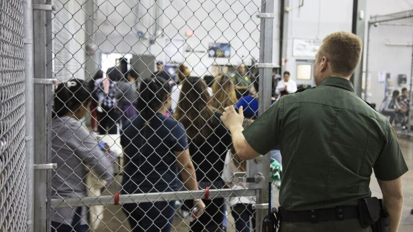 In this photo provided by U.S. Customs and Border Protection, a U.S. Border Patrol agent watches as