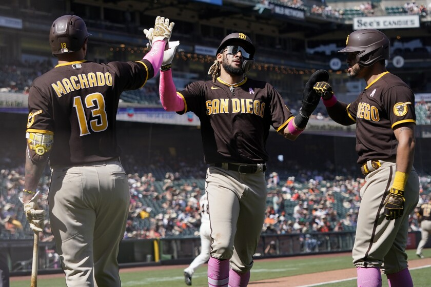 San Diego Padres' Fernando Tatis Jr., middle, and Tommy Pham, right, are congratulated by Manny Machado (13) after both scored on a two-run triple hit by Trent Grisham during the eighth inning of a baseball game against the San Francisco Giants in San Francisco, Sunday, May 9, 2021. (AP Photo/Jeff Chiu)