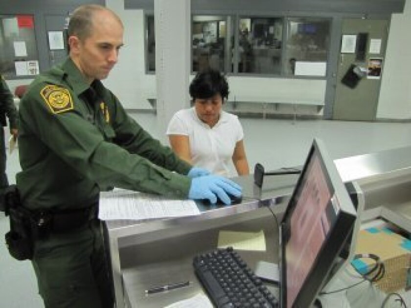 A Border Patrol agent books a woman into a short-term detention center in Nogales, Ariz. In anonymous surveys of recent migrants, many have reported inhumane conditions in Border Patrol cells, including extreme cold, overcrowding, and inadequate food, water and toilet facilities. Credit: Peter O'Dowd/Fronteras