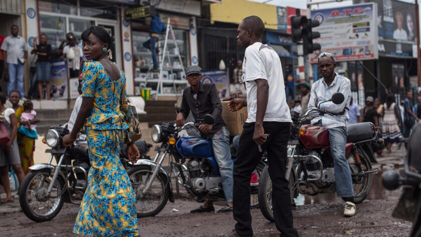 A woman crosses a street in the Matonge district of Kinshasa, the Congolese capital that is home to more than 10 million people, in March 2015.