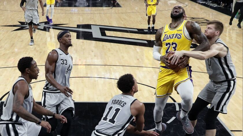 Lakers forward LeBron James (23) is fouled by San Antonio Spurs forward Davis Bertans, right, during the first half.
