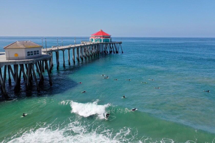 Surfers off the Huntington Beach Pier on Friday ignore the governor's order to close Orange County beaches.