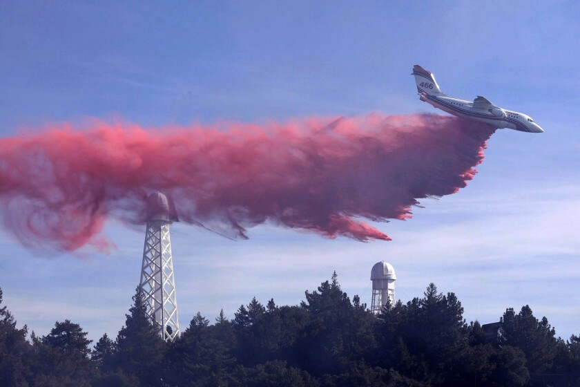 An air tanker drops fire retardant over the Mt. Wilson Observatory as firefighters work to extinguish a fire in the Angeles National Forest.