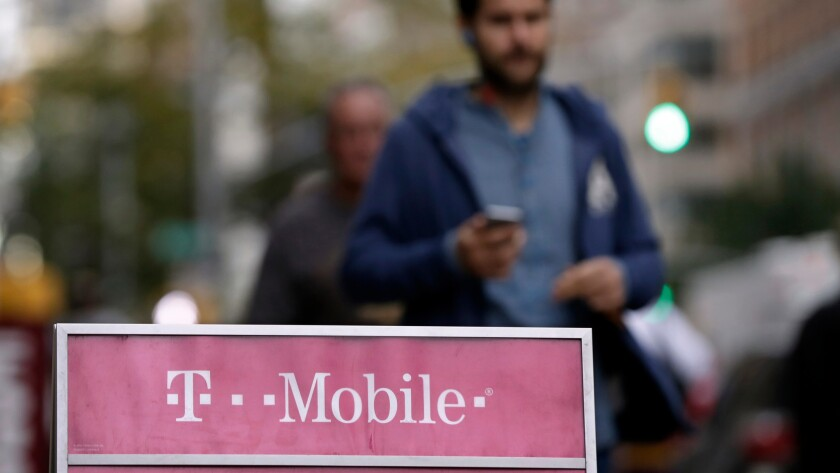 People walk past a T-Mobile store in New York in 2015.