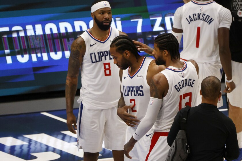 Clippers forward Kawhi Leonard is congratulated by teammates Paul George and Marcus Morris (8) after Game 6 in Dallas.