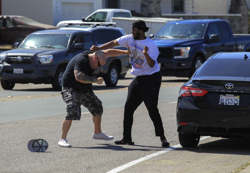 A man from the pro-Trump gathering, left, and a man from the Black Lives Matter protest have a short scuffle in La Mesa.