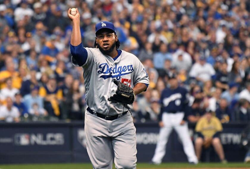 Dodgers relief pitcher Pedro Baez records an out at first base during Saturday's game against Milwaukee.