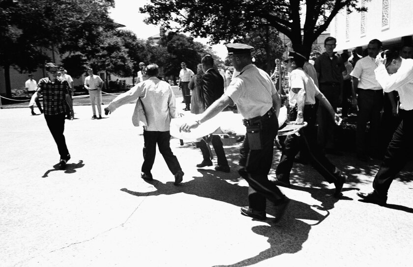 FILE - In this Aug. 1, 1966 file photo, one of the victims of Charles Joseph Whitman, the sniper who gunned down victims from a perch in the University of Texas tower, is carried across the campus to a waiting ambulance in Austin. The unidentified victim was gunned down inside the tower, according