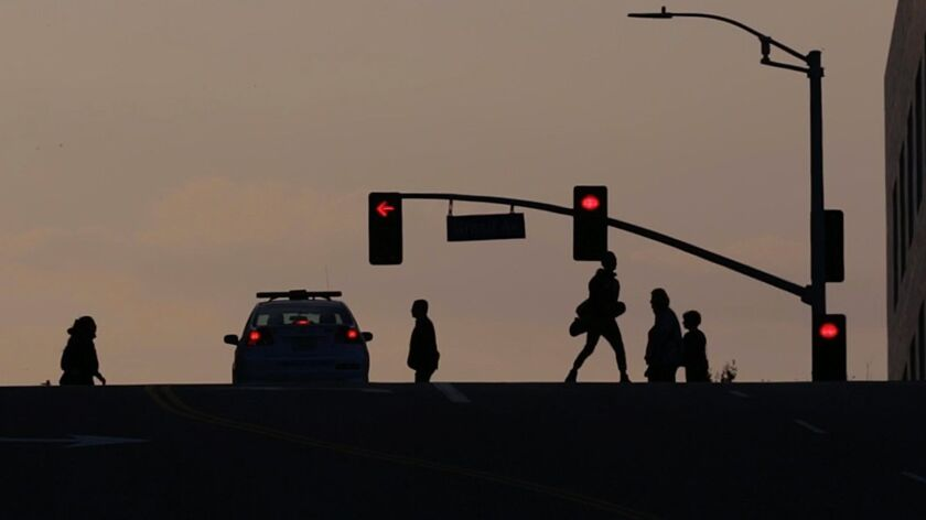 LOS ANGELES, CA - April 23, 2015: As dusk settles in, pedestrians cross at the intersection of Grand