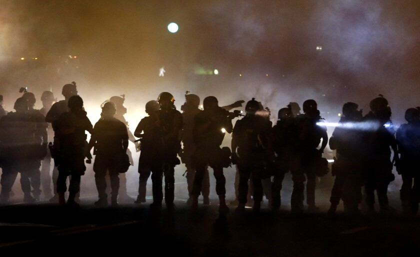 Police walk through a cloud of smoke as they clash with protesters in Ferguson, Mo., on Aug. 13, 2014.