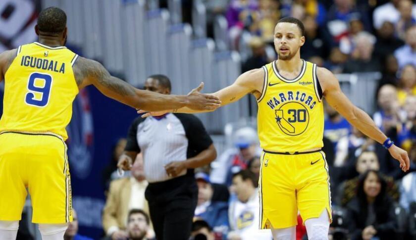 El guardia de Golden State Warriors Stephen Curry (d) y Andre Iguodala (i) celebran su anotación contra contra los Washington Wizards durante la primera mitad del partido de baloncesto de la NBA entre los Golden State Warriors y los Washington Wizards en el CapitalOne Arena de Washington, DC, EE. UU., este jueves. EFE