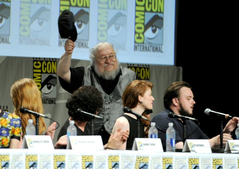 """George R.R. Martin attends the """"Game of Thrones"""" panel on Day 2 of Comic-Con International on Friday, July 25, 2014, in San Diego. Looking on from left are Sophie Turner, Kit Harington, Rose Leslie and John Bradley. (Photo by Chris Pizzello/Invision/AP)"""