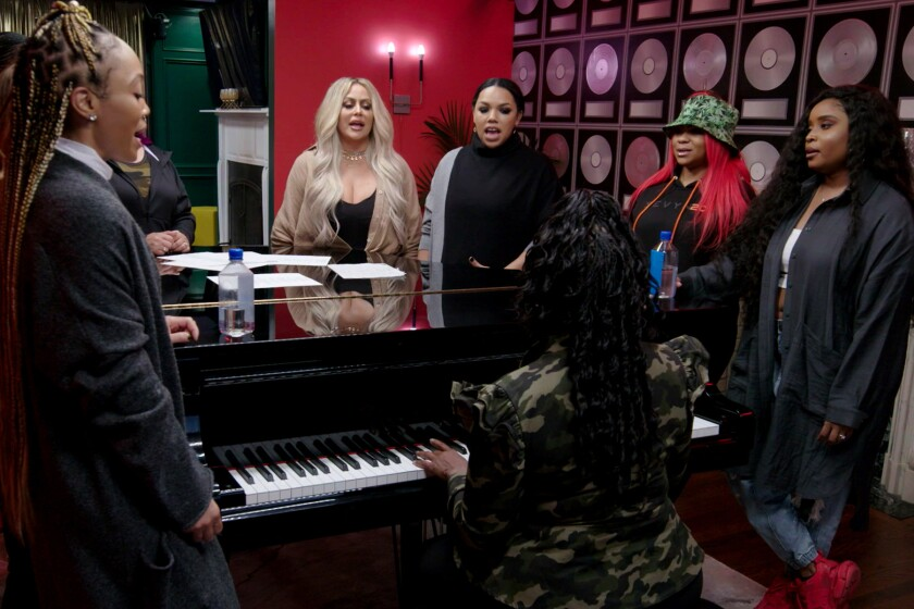 A group of women stand around a piano and sing while one woman plays.