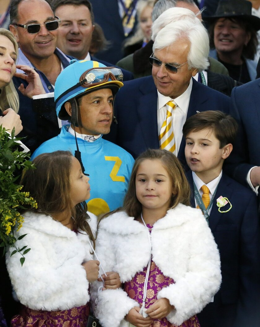 Jockey Victor Espinoza talks with trainer Bob Baffert, top right, after Espinoza rode American Pharoah to victory in the Breeders' Cup Classic horse race at Keeneland race track Saturday, Oct. 31, 2015, in Lexington, Ky. (AP Photo/Brynn Anderson)